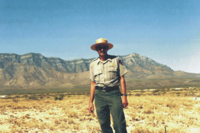 A Ranger in front of mountain range surrounding White Sands National Monument - Lake Lucero